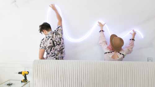A man and a woman installing a LED neon sign