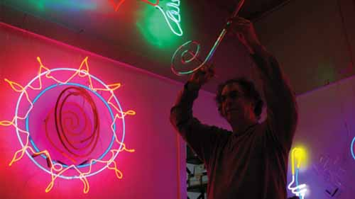 A man hanging a neon sign