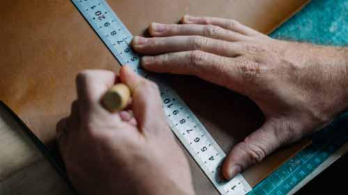 A person measuring a board
