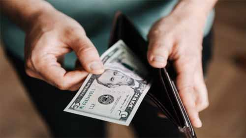 A person taking money out of a wallet
