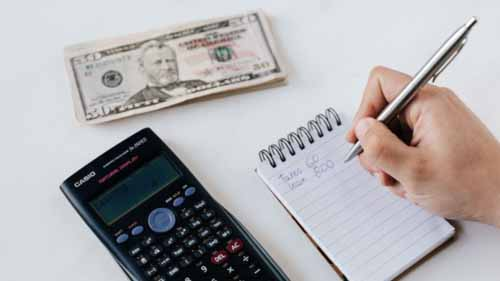 A person writes a budget next to a wad of bills and a calculator