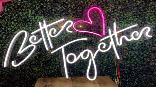 An LED neon sign in front of a green backdrop